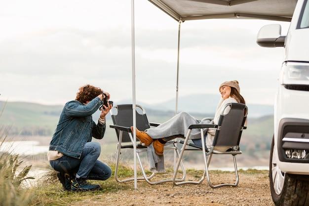 Paar genieten van de natuur tijdens een road trip met auto en camera Gratis Foto
