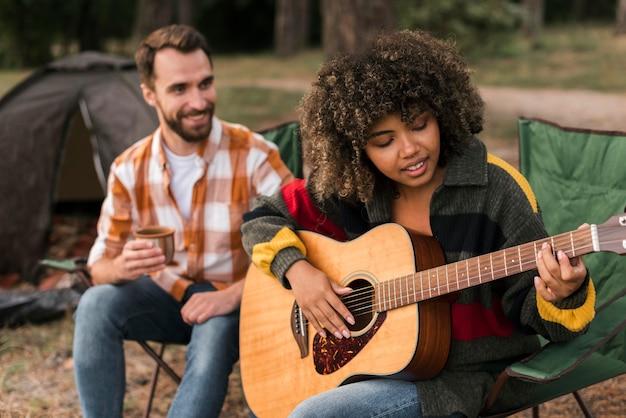 Paar gitaarspelen tijdens het kamperen buiten Gratis Foto