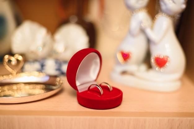 Paar gouden trouwringen liggen in een rode doos Premium Foto