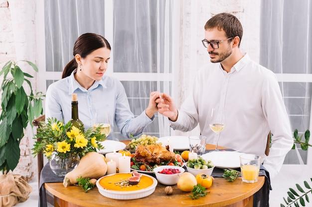Paar hand in hand aan feestelijke tafel Gratis Foto