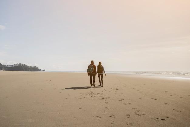 Paar hand in hand en wandelen op het strand Gratis Foto