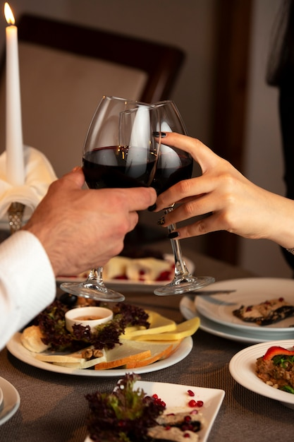 Paar handen juichen rode wijnglazen tijdens het diner Gratis Foto