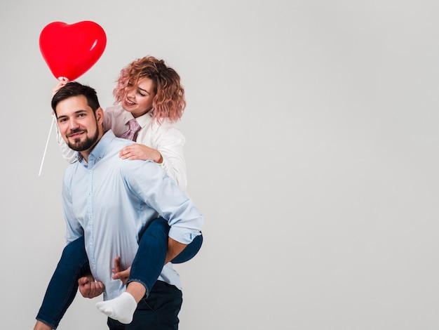 Paar het stellen met ballon voor valentijnskaarten Gratis Foto