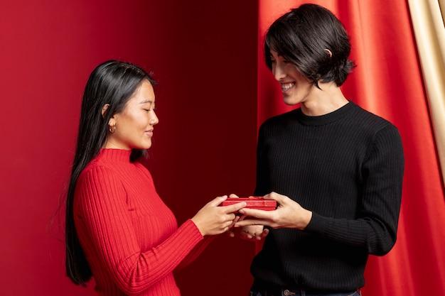 Paar het stellen met gift voor chinees nieuw jaar Gratis Foto