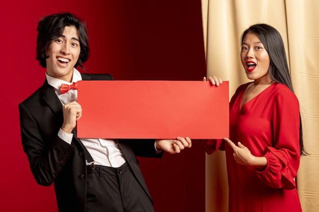 Paar het stellen met rood envelopmodel voor chinees nieuw jaar Gratis Foto