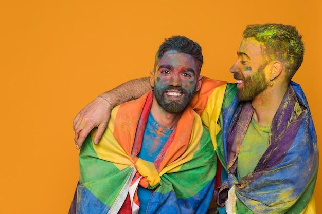Paar homoseksuele mannen gedekt door lgbt-vlag en kleurrijk geschilderd Gratis Foto