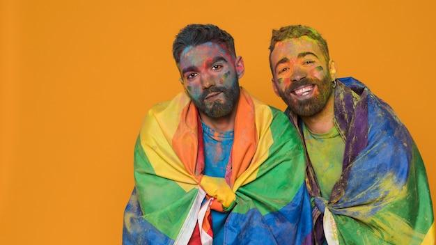 Paar homoseksuele mannen in kunstverf gedekt door lgbt-vlag Gratis Foto