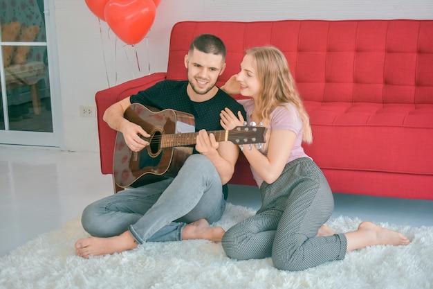Paar houden van gitaar spelen in slaapkamer liefde in valentijnsdag concept Premium Foto