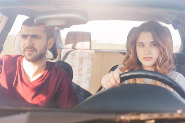 Paar in auto op road trip: geconcentreerde ervaren vrouwelijke bestuurder zit achter het stuur en haar man Gratis Foto