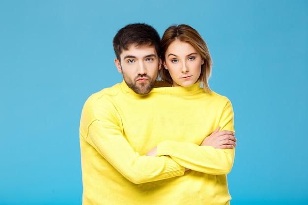 Paar in gele trui poseren met gekruiste armen over blauwe muur Gratis Foto