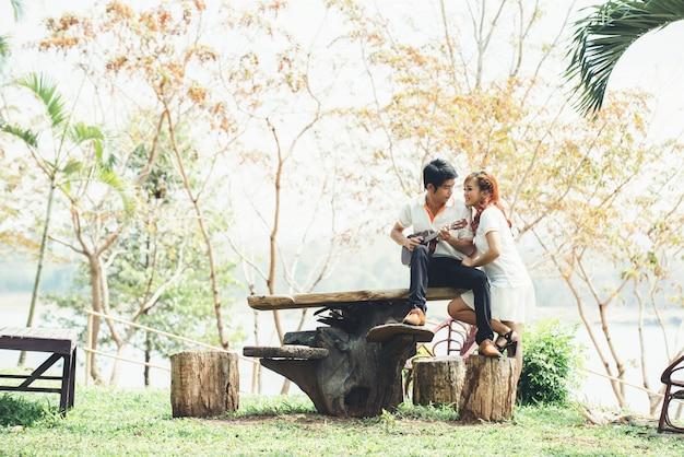 Paar in liefde met gitaarspelen in de natuur Gratis Foto