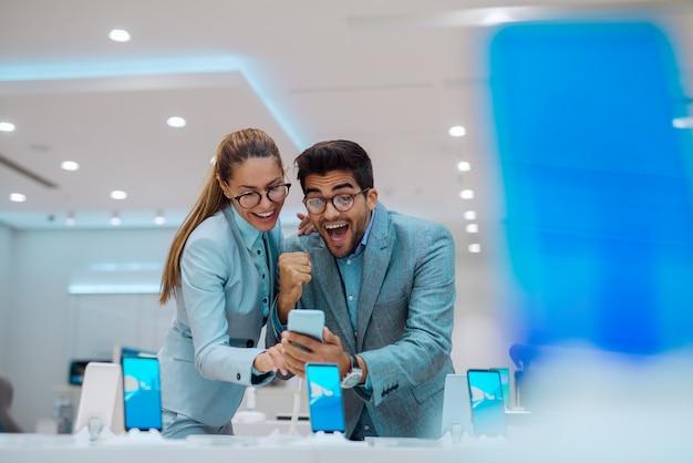 Paar in tech winkel op zoek naar een nieuwe mobiele telefoon. Premium Foto