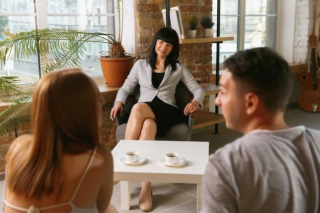Paar in therapie of huwelijkstherapie. psycholoog, vertrouwenspersoon, therapeut of relatieadviseur die advies geeft. man en vrouw zittend op een sessie psychotherapie. familie, geestelijke gezondheidsconcept. Gratis Foto