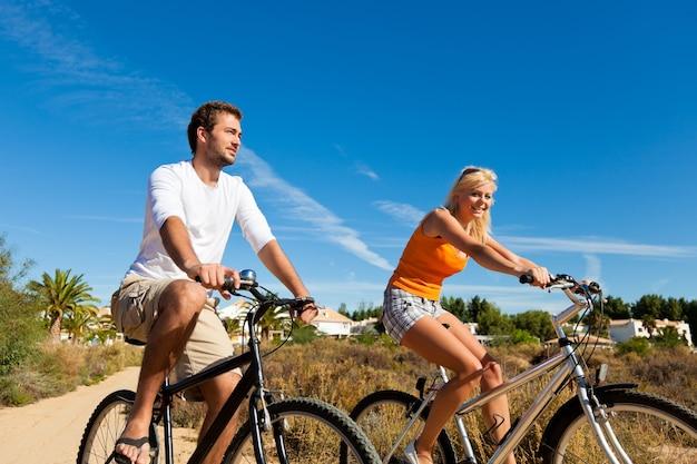 Paar in vakantie fietsen op strand Premium Foto