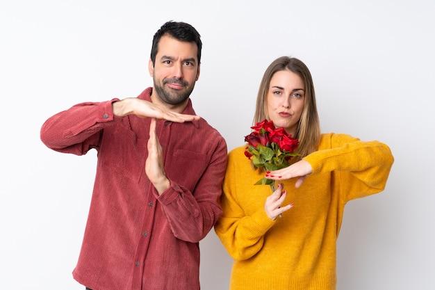 Paar in valentijnsdag bedrijf bloemen over geïsoleerde muur maken stop gebaar met haar hand om een handeling te stoppen Premium Foto