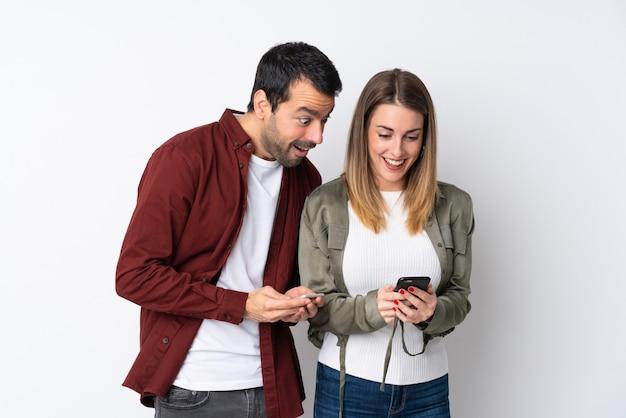 Paar in valentijnsdag over geïsoleerde muur verzenden van een bericht of e-mail met de mobiel Premium Foto