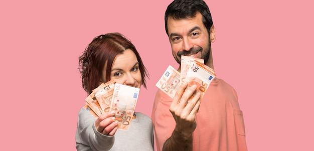 Paar in valentijnskaartdag die heel wat geld over geïsoleerde roze achtergrond neemt Premium Foto