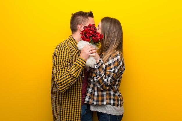 Paar in valentijnskaartdag met bloemen en het kussen Premium Foto