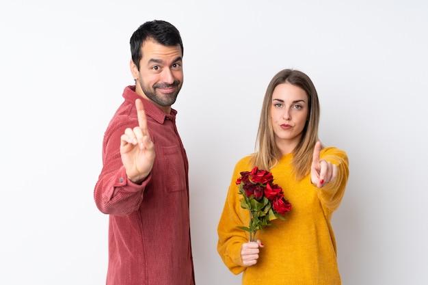 Paar in valentine day-holdingsbloemen over geïsoleerde muur die en een vinger tonen opheffen Premium Foto
