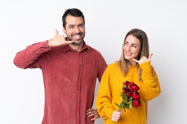 Paar in valentine day-holdingsbloemen over geïsoleerde muur die telefoongebaar maken. bel me terug teken Premium Foto