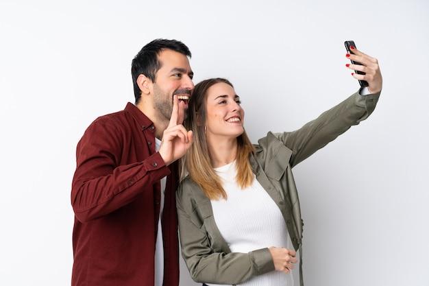Paar in valentine day over geïsoleerde muur die een selfie met mobiel maken Premium Foto