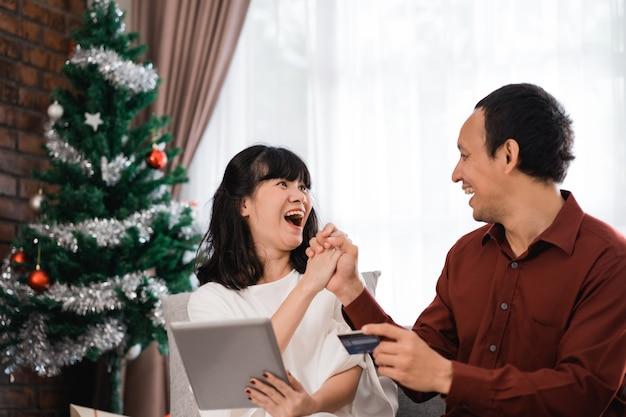Paar jagen voor kerstverkoop deal in online markt. modern winkelen met creditcardbetaling Premium Foto