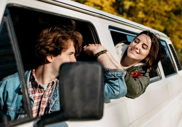 Paar kijken elkaar aan vanuit een busje Gratis Foto
