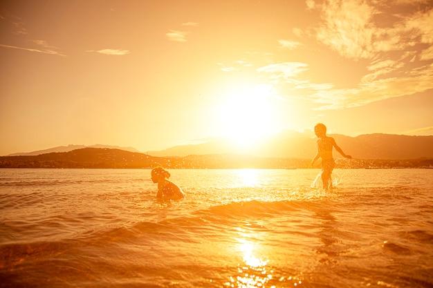 Paar kinderen die in het overzees spelen, schot dat bij zonsondergang wordt genomen Premium Foto
