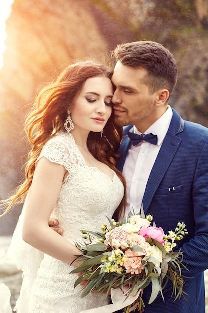 Paar knuffelen bij zonsondergang, verliefde paar kussen in zonsondergang. huwelijksceremonie buitenshuis Premium Foto