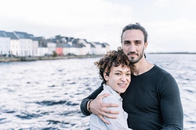 Paar knuffelen elkaar met de zee onscherp Gratis Foto