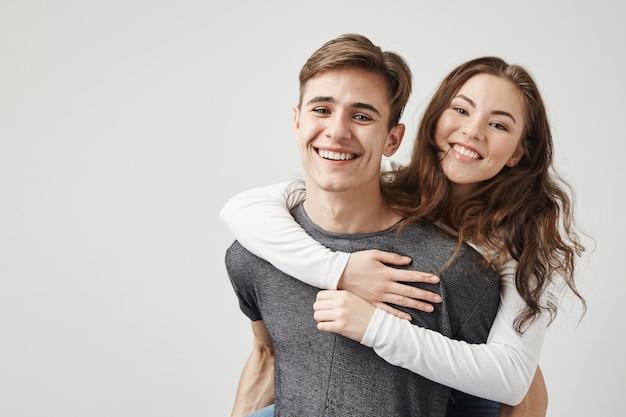 Paar knuffelen en lachen in de buurt van de muur. Gratis Foto