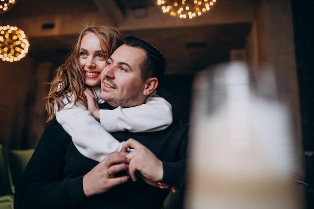 Paar knuffelen en zitten samen in een café Gratis Foto