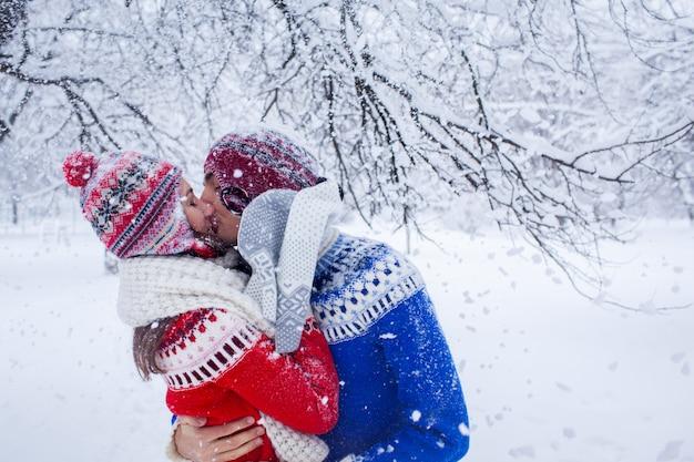Paar knuffels en kusjes in winter forest Premium Foto