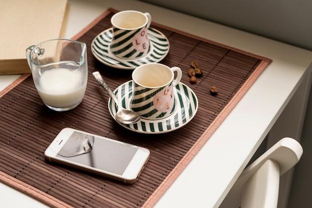 Paar koffiekopjes met een smartphone op tafel Gratis Foto