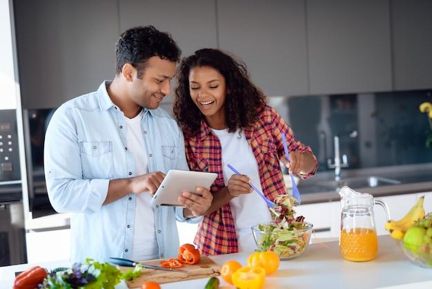 Paar kokende salade en het gebruiken van tablet op keuken Premium Foto