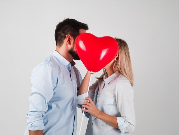 Paar kussen achter ballon voor valentijnskaarten Gratis Foto