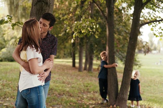 Paar kussen terwijl hun kinderen buitenshuis kijken Gratis Foto