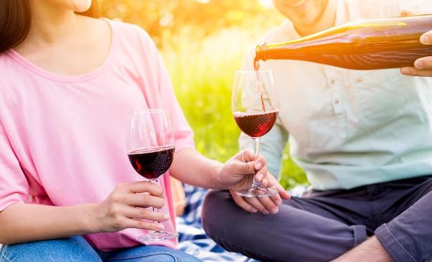Paar liefhebbers die rode wijn drinken op picknick Gratis Foto