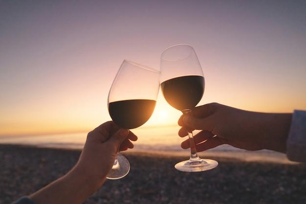 Paar liefhebbers drinken van rode wijn tijdens het kijken naar zonsondergang en genieten van zee vakantie op huwelijksreis Premium Foto