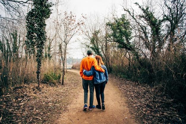 Paar lopen samen op grind bospad Gratis Foto