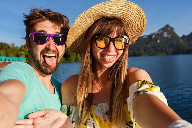 Paar markering selfie in de buurt van geweldig uitzicht op het meer en de bergen, stijlvolle kleding en accessoires dragen. speelse vrolijke sfeer. Gratis Foto