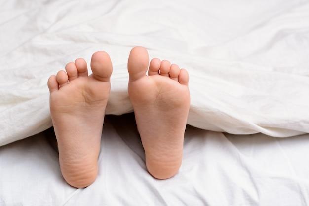 Paar meisje` s voeten in een bed Premium Foto