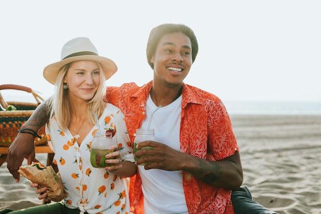 Paar met een picknick op het strand Premium Foto