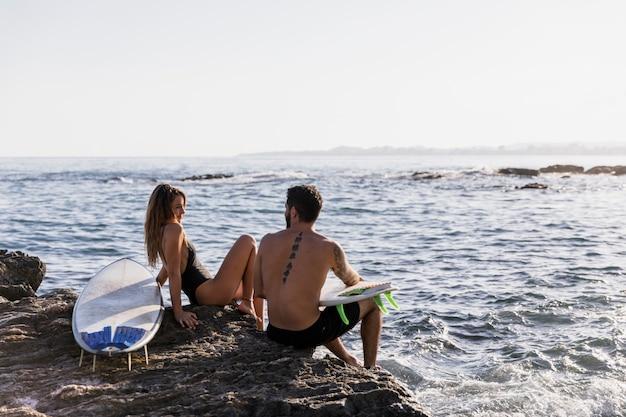 Paar met surfplanken die elkaar op kust bekijken Gratis Foto