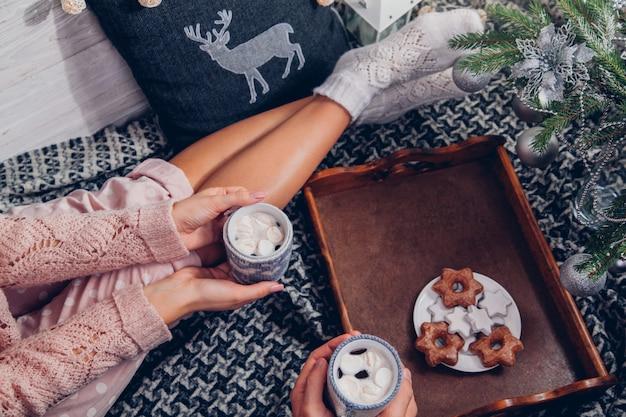 Paar met warme chocolademelk onder de kerstboom Premium Foto