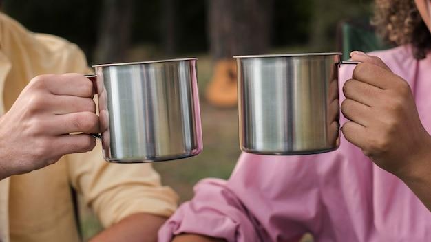 Paar met warme dranken tijdens het kamperen buiten Gratis Foto