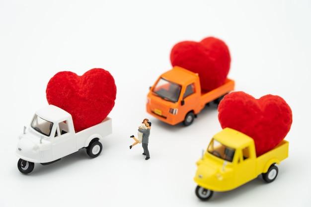 Paar miniatuur mensen staan met rood hart is de belofte van liefde. Premium Foto