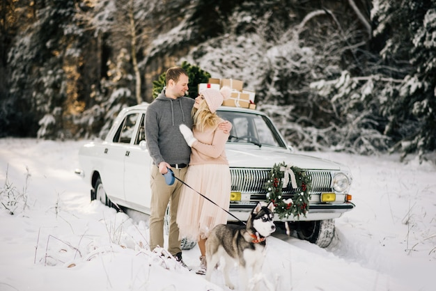 Paar naast auto met husky in de winter Premium Foto