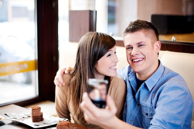 Paar nemen foto in café Gratis Foto