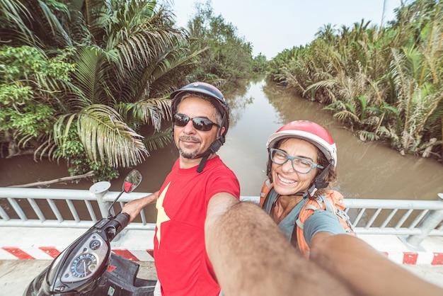 Paar nemen selfie op motor. man en vrouw met helm het biking in het mekong deltagebied, zuid-vietnam. weelderig groen kokospalmbos en waterkanaal. Premium Foto